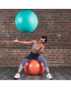 Davina McCall Gym Ball with Pump, available in blue, yellow or Orange & in size 65 cm or 75 cm diameter. Davina is sit on an orange ball and is throwing a blue ball