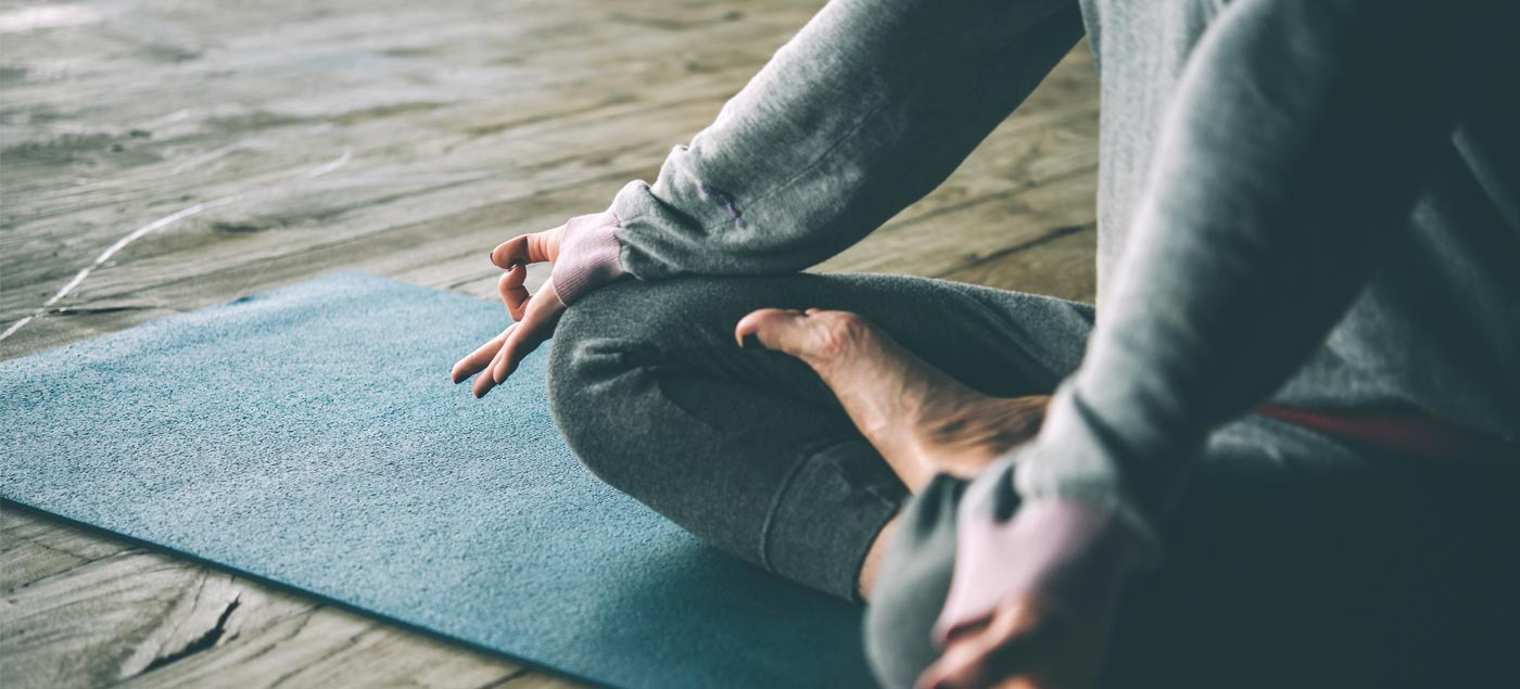 Someone going yoga on a blue yoga mat on a wooden floor