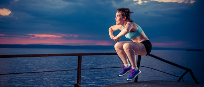 person doing a squat jump in front of a sunset by the sea