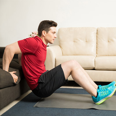 person performing a triceps dip on a sofa