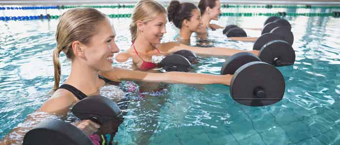 Women moving dumbbells in the water
