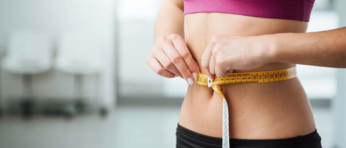 person measuring their stomach with a measuring tape