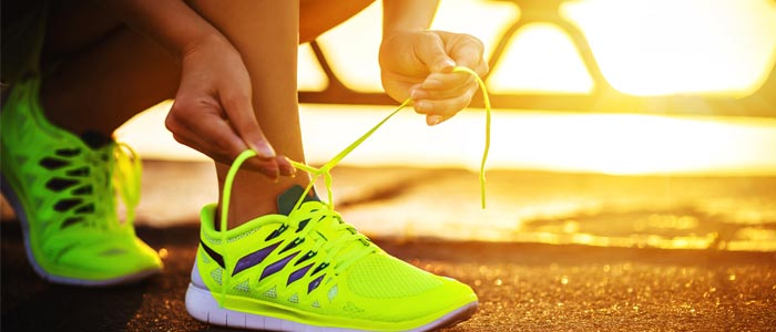 a person lacing up bright green trainers