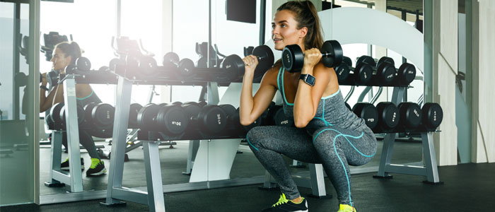 a person squatting with dumbbells