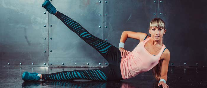 person lying on their side doing a leg raise in front of a grey background