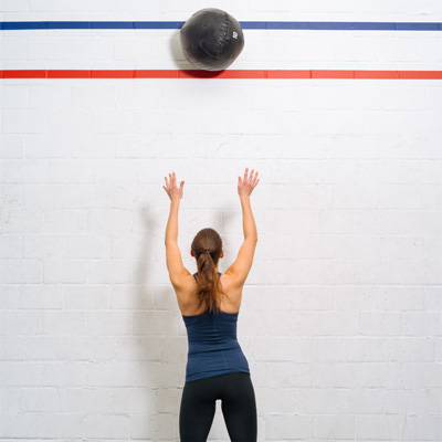 person throwing a medicine ball up against the wall