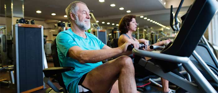 people on recumbent exercise bikes in a gym