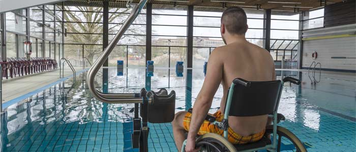 Man in wheelchair preparing to enter a swimming pool