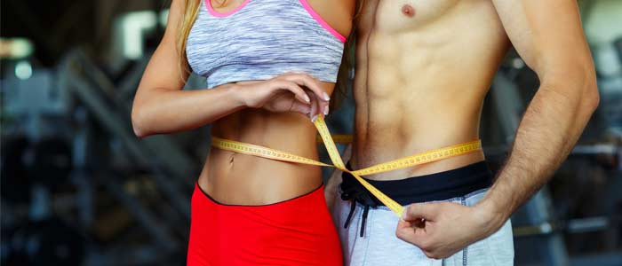 People measuring their waist line for their weight loss results