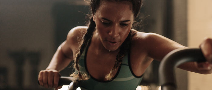 Woman sweating whilst working out on an assault bike