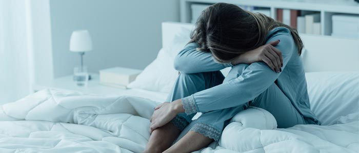 Woman looking sad in her bed