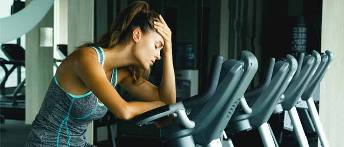 Woman tired at exercise bike