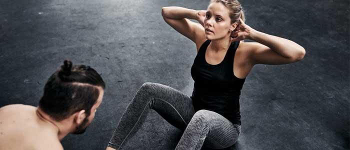 Man coaching woman through crunches