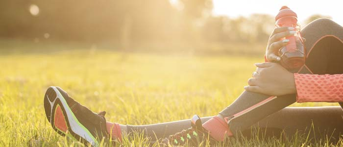 Woman holding leg whilst sat in a scenic field post run