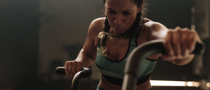 woman working hard on cross trainer
