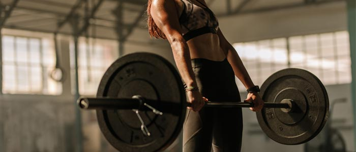Woman performing a dead lift with a heavy weight