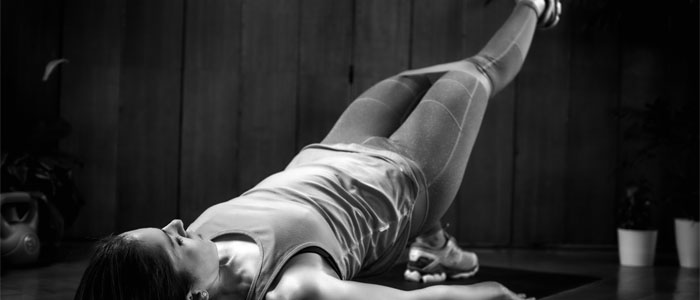 Woman performing single leg glute bridge