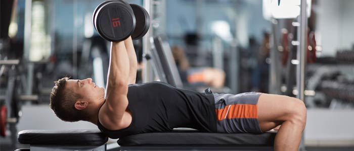 Man performing a dumbbell bench press chest exercise