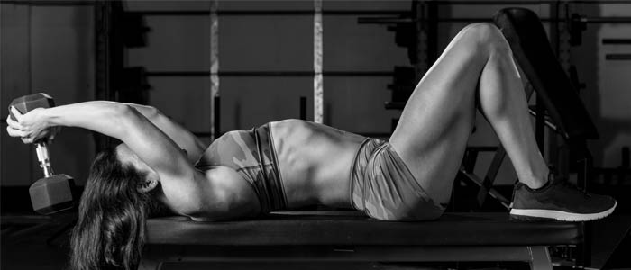woman performing a dumbbell pullover in the chest and triceps workout