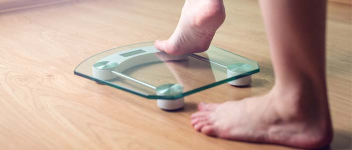 Feet on a glass scales for weight progress tracking