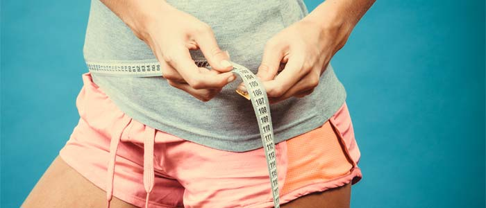 Person tracking their fitness progress with waistline measurements