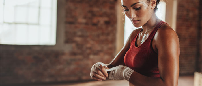 Woman wrapping hands before boxing