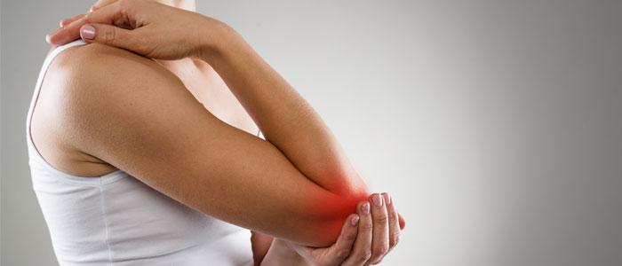 woman holding injured elbow