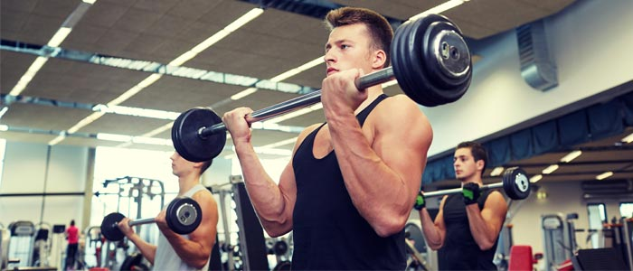 Man performing barbell bicep curl in a gym