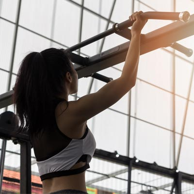 Woman performing chin ups in a gym