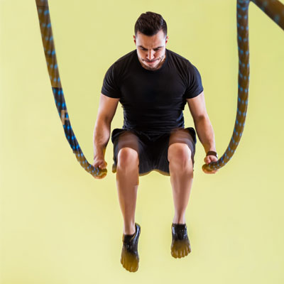 Man jumping with battle ropes