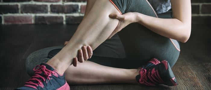Woman holding her calf muscle from muscle soreness