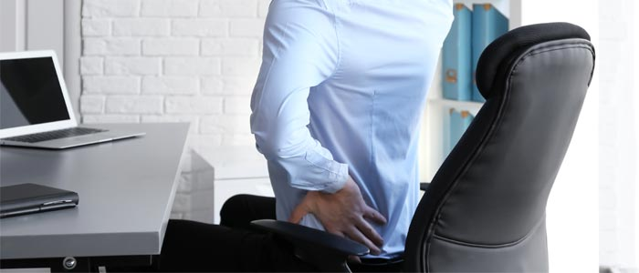 Main holding back in pain while sat in an office chair