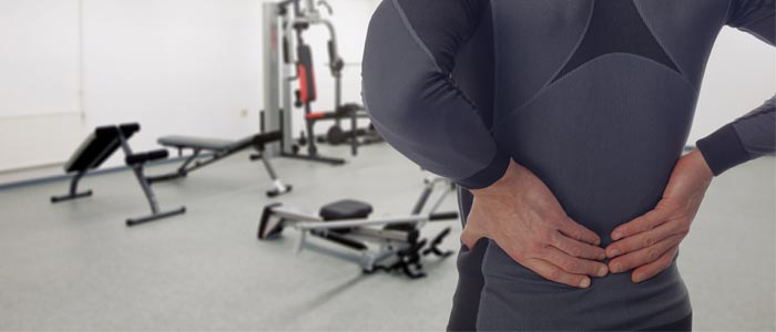 Man holding his lower back in a gym