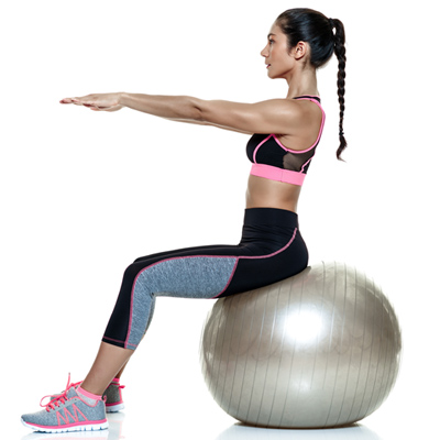 Woman performing Russian twists on n exercise ball