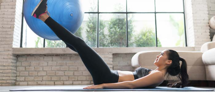 Woman liftin up an exercise ball with her legs