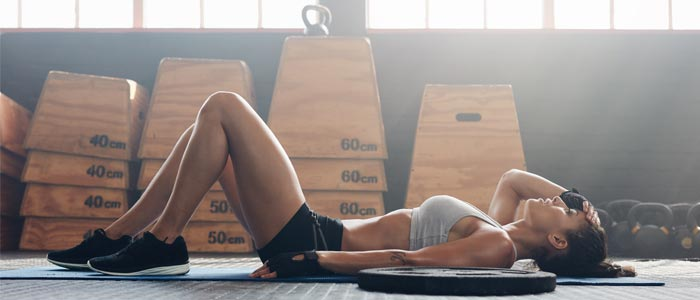 Woman fatigued on the floor after training