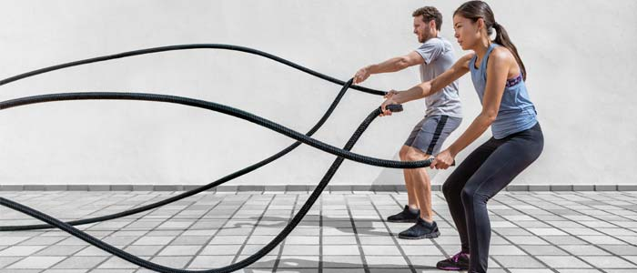Man and woman using battle ropes