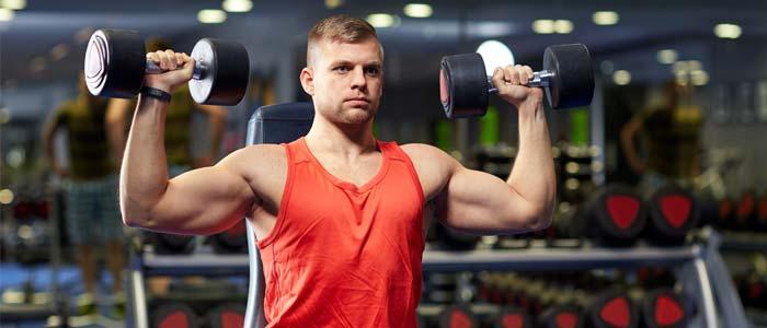 Man shoulder pressing dumbbells