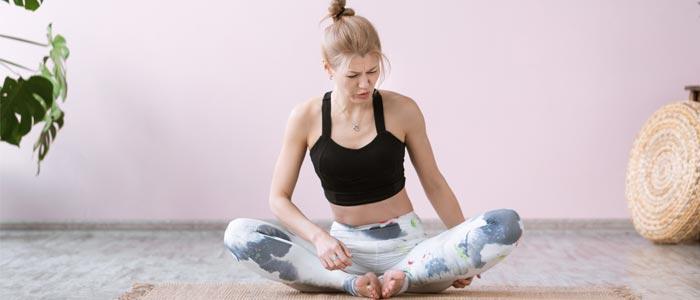 Woman in pain sat cross legged