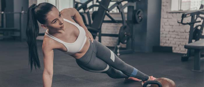 Woman doing side plank in a gym