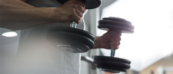 Close up of man holding dumbbells