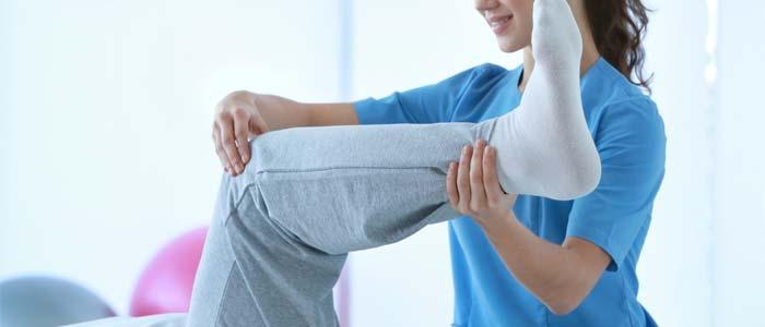 Woman raising patients leg up