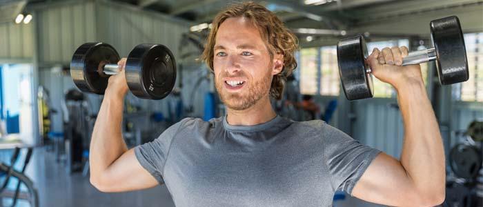 Man shoulder pressing dumbbells in a gym