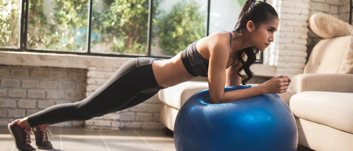 woman strengthening her core doing an exercise ball plank