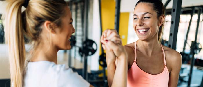 Two women looking happy in the gym