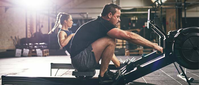 Two people using rowing machines