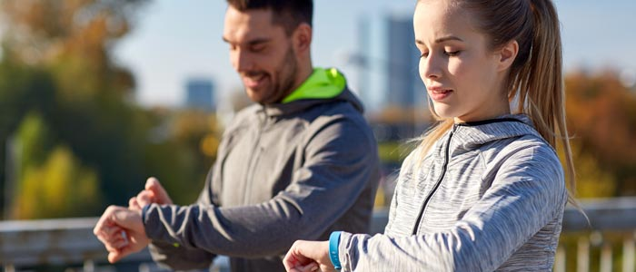Man and Mand and woman using their fitness trackers outside