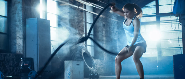 woman exercising with battle ropes