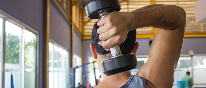 man holding dumbbell behind his head