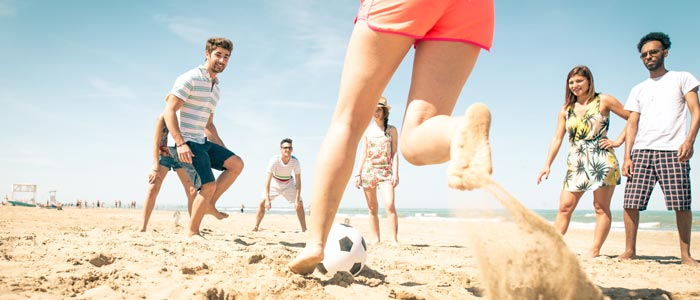 group of friends playing football on the beach